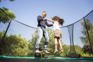 family jumping on trampoline during covid lockdown