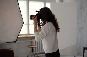 Young woman filming explainer video instructions in a studio with professional lighting