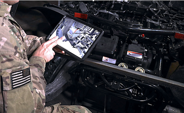 Depiction of military personnel using BILT 3D interactive instructions while on maintenance duty